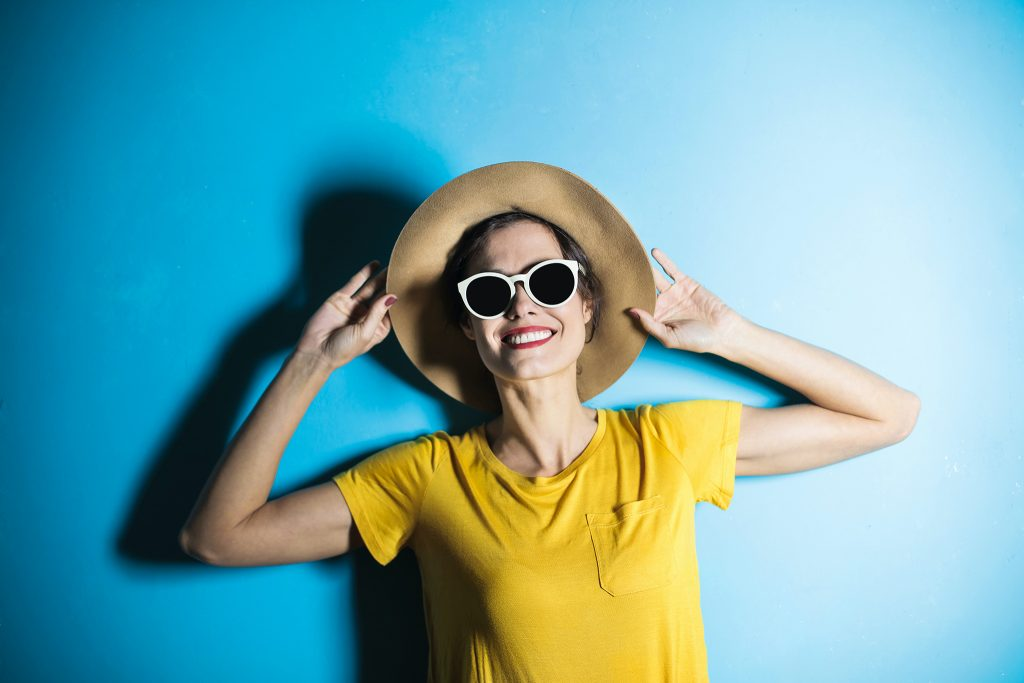 Smiling woman in sunglasses and a hat on a blue background - wearing all the hats as a business owner, on the Creative Reboot podcast