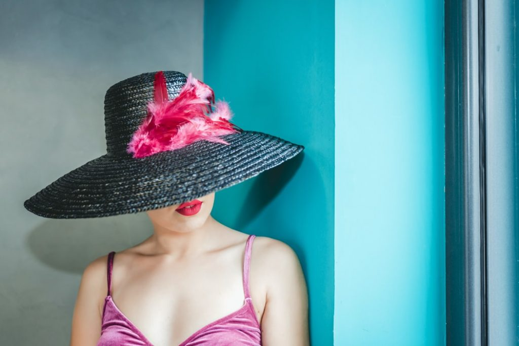 Woman leaning against a wall wearing a black hat with pink feathers - wearing all the hats in business podcast episode
